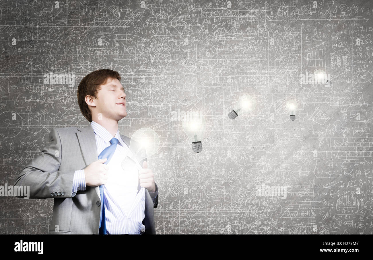 Young businessman opening chest and acting like super hero Stock Photo