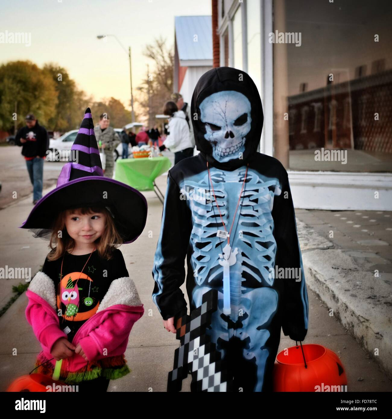 Person In Monster Costume Standing By Cute Girl On Footpath During Halloween Stock Photo
