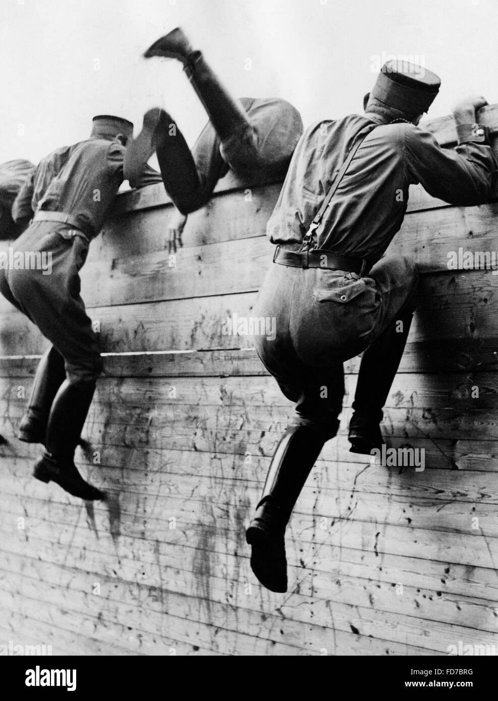 SA men climbing a wall, undated - Stock Image