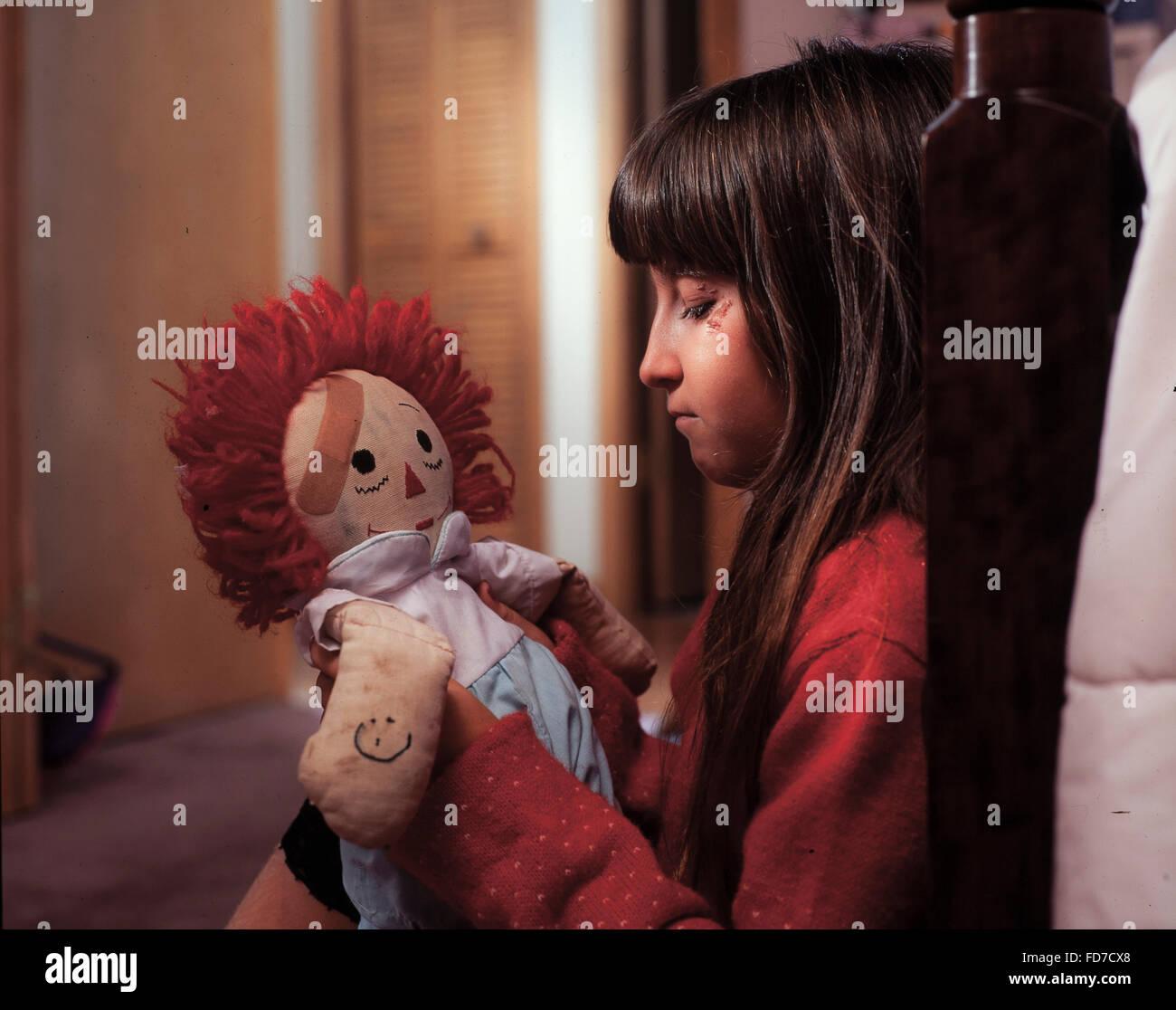 Sad young injured girl with bandaged doll. - Stock Image