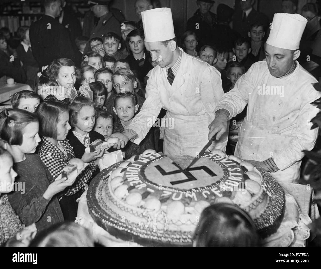 The birthday cake of Adolf Hitler is shared with children,1939 Stock Photo