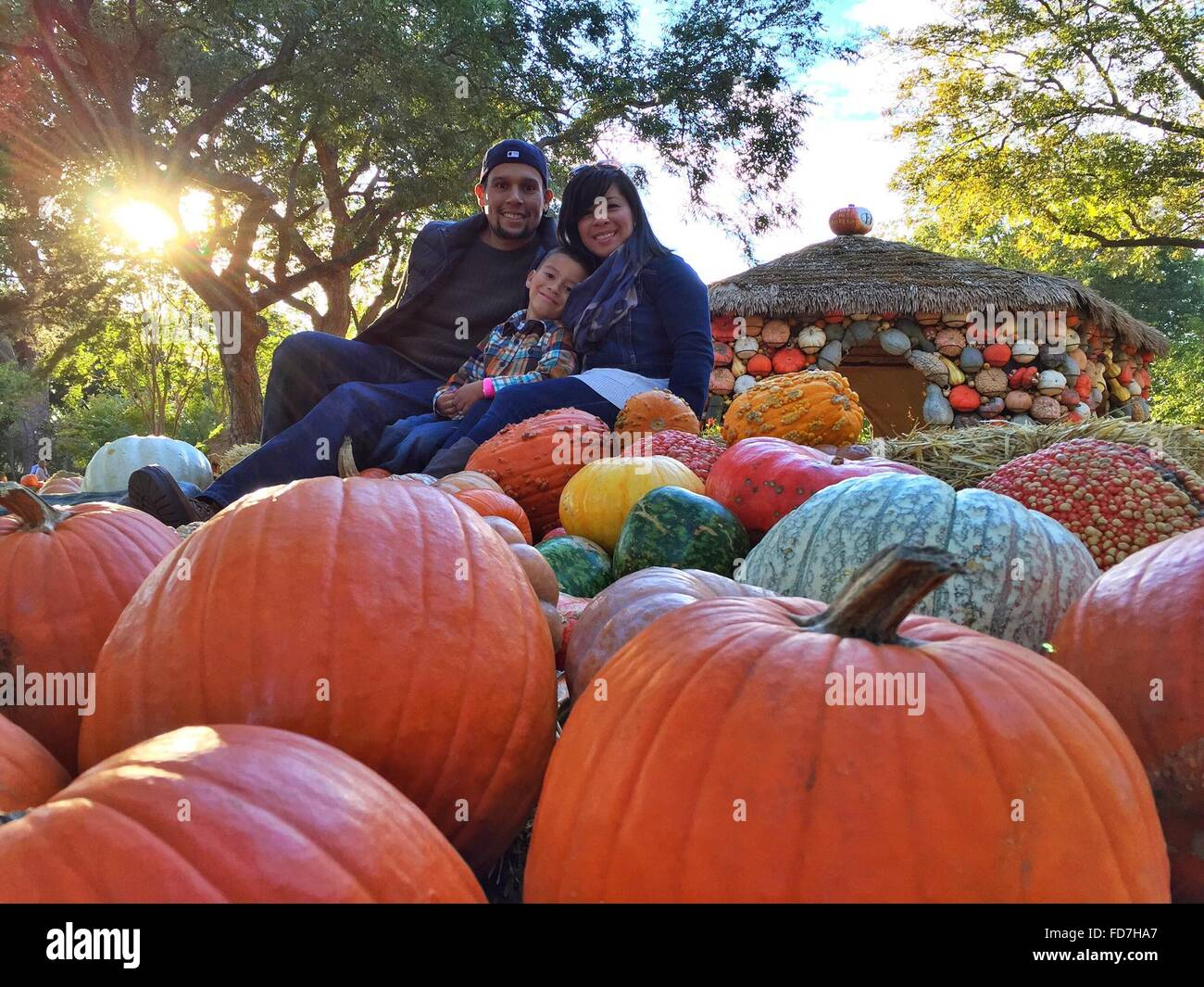 Portrait Of Smiling Family With Pumpkins At Village - Stock Image
