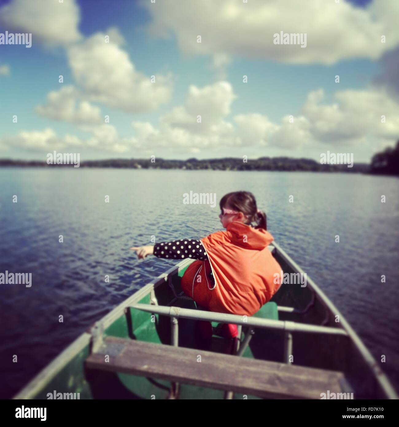 Rear View Of Girl In Boat Showing Something At Lake - Stock Image
