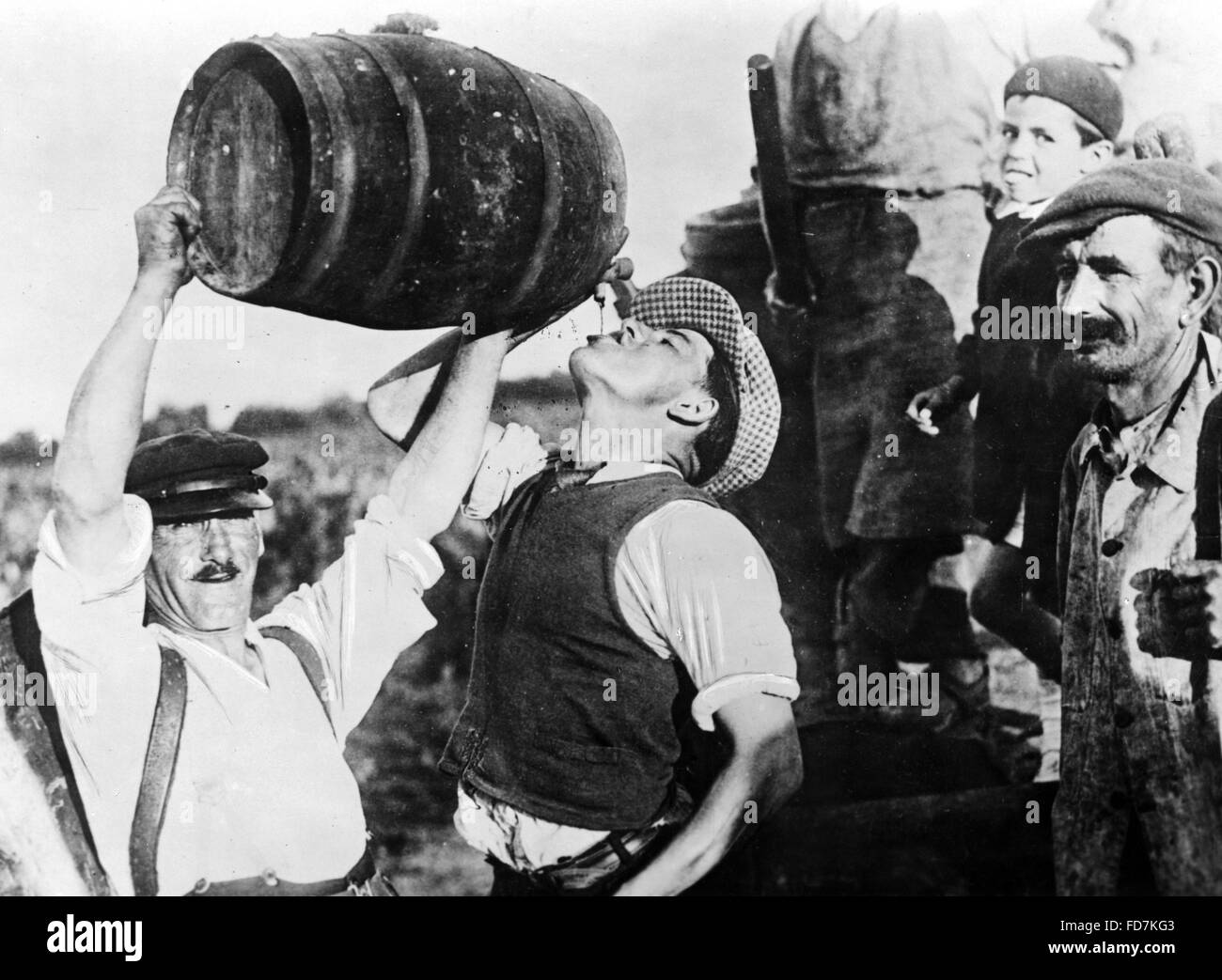 Man drinking wine during grape harvest in France, 1940 Stock Photo
