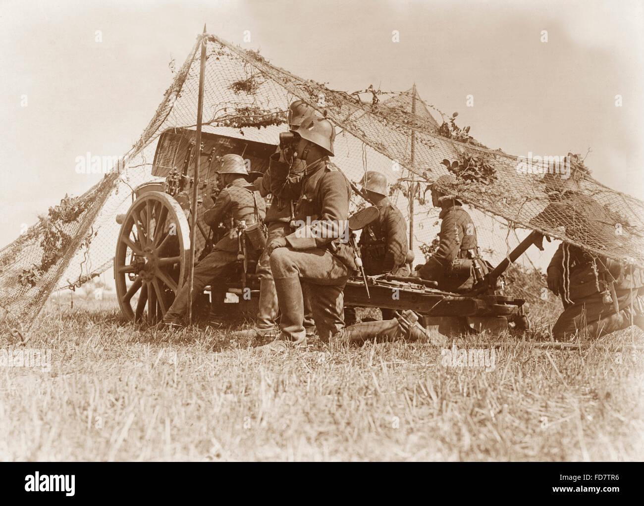 Reichswehr soldier with gun under camouflage netting - Stock Image