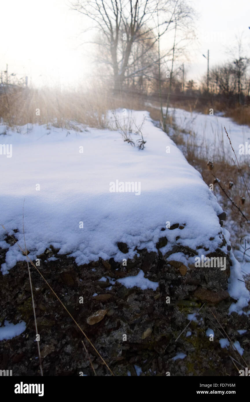 closeup of the snow covered concrete ruined substructure at sunny winter morning - Stock Image