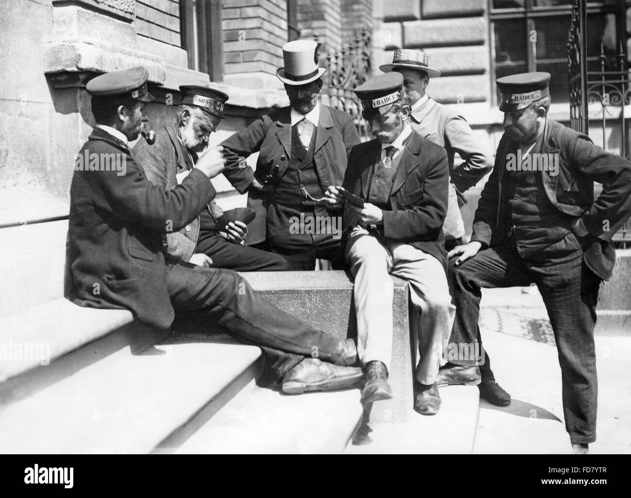 Porters playing cards in front of the south entrance to the Central Station in Munich, 1906 - Stock Image