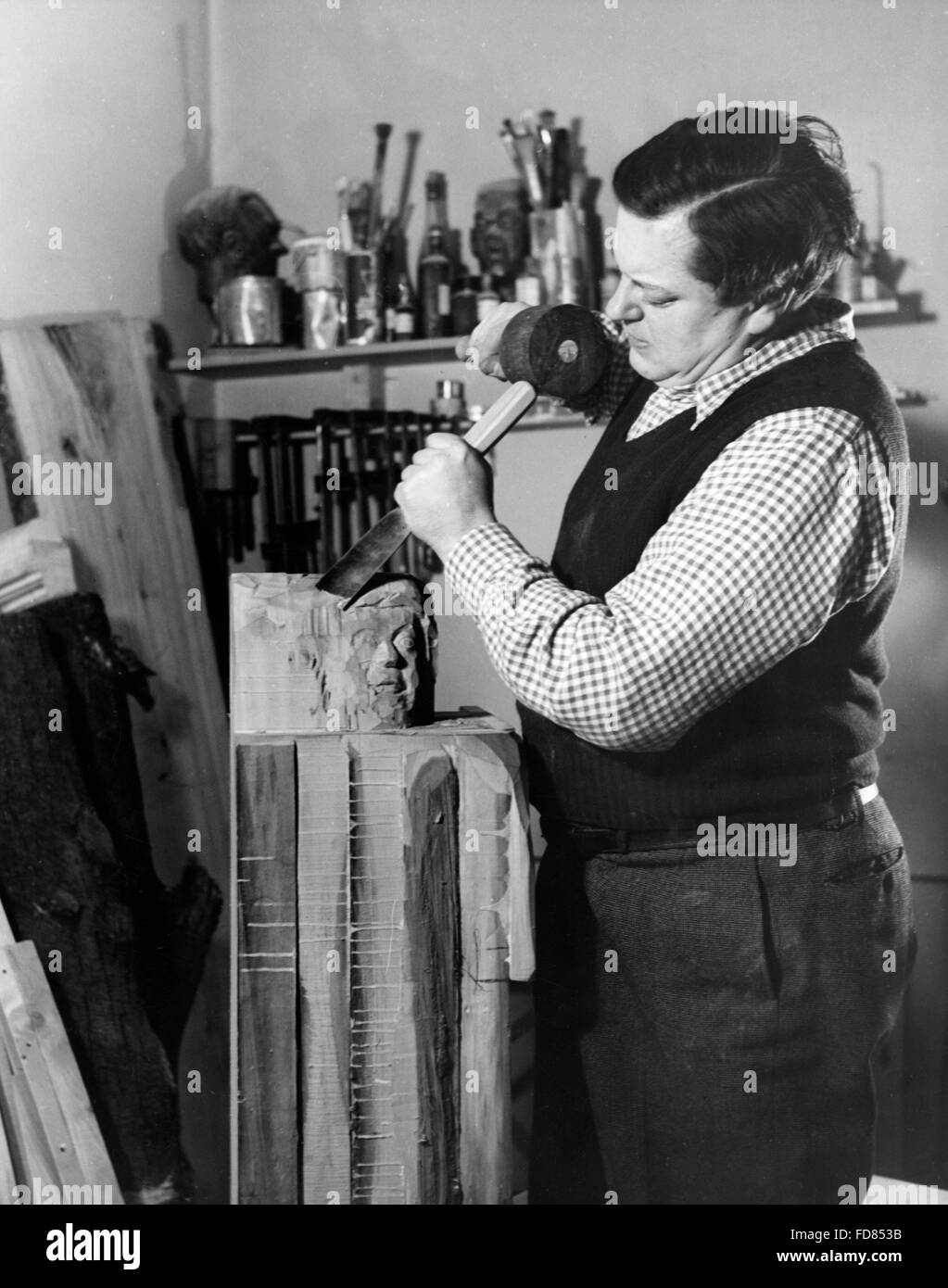 Paul Dahlke works on a wood sculpture, 1941 - Stock Image