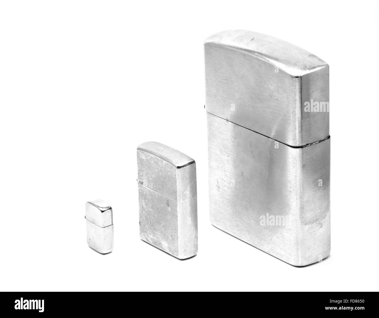 Three different sizes of metallic lighters with cap closed - Stock Image