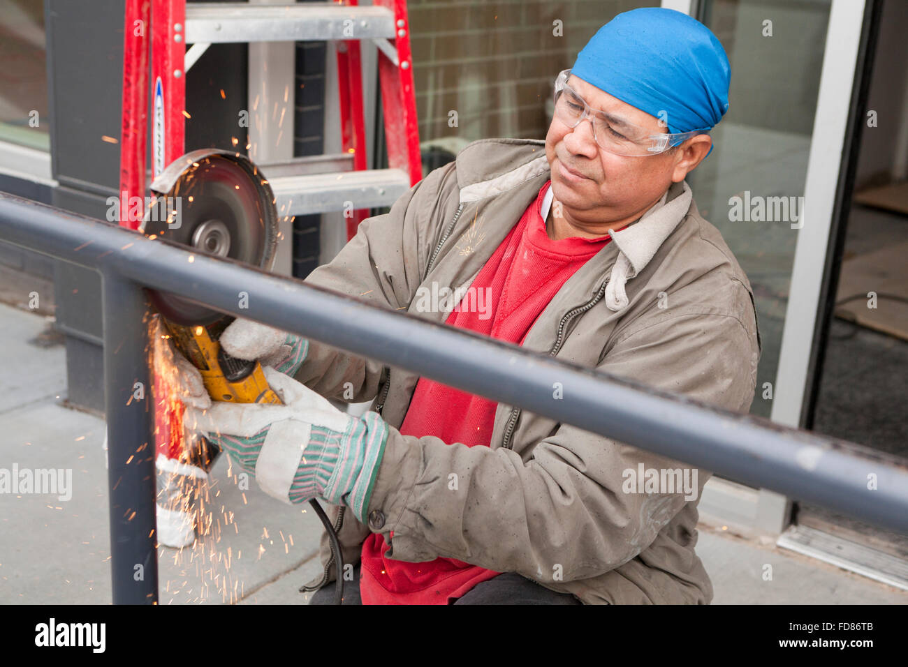 Construction worker cutting steel pipe with angle grinder tool - USA Stock Photo