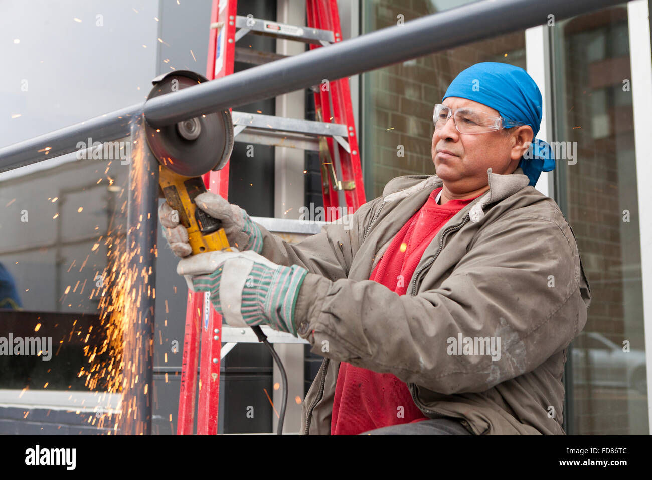 Construction worker cutting steel pipe with angle grinder tool - USA - Stock Image