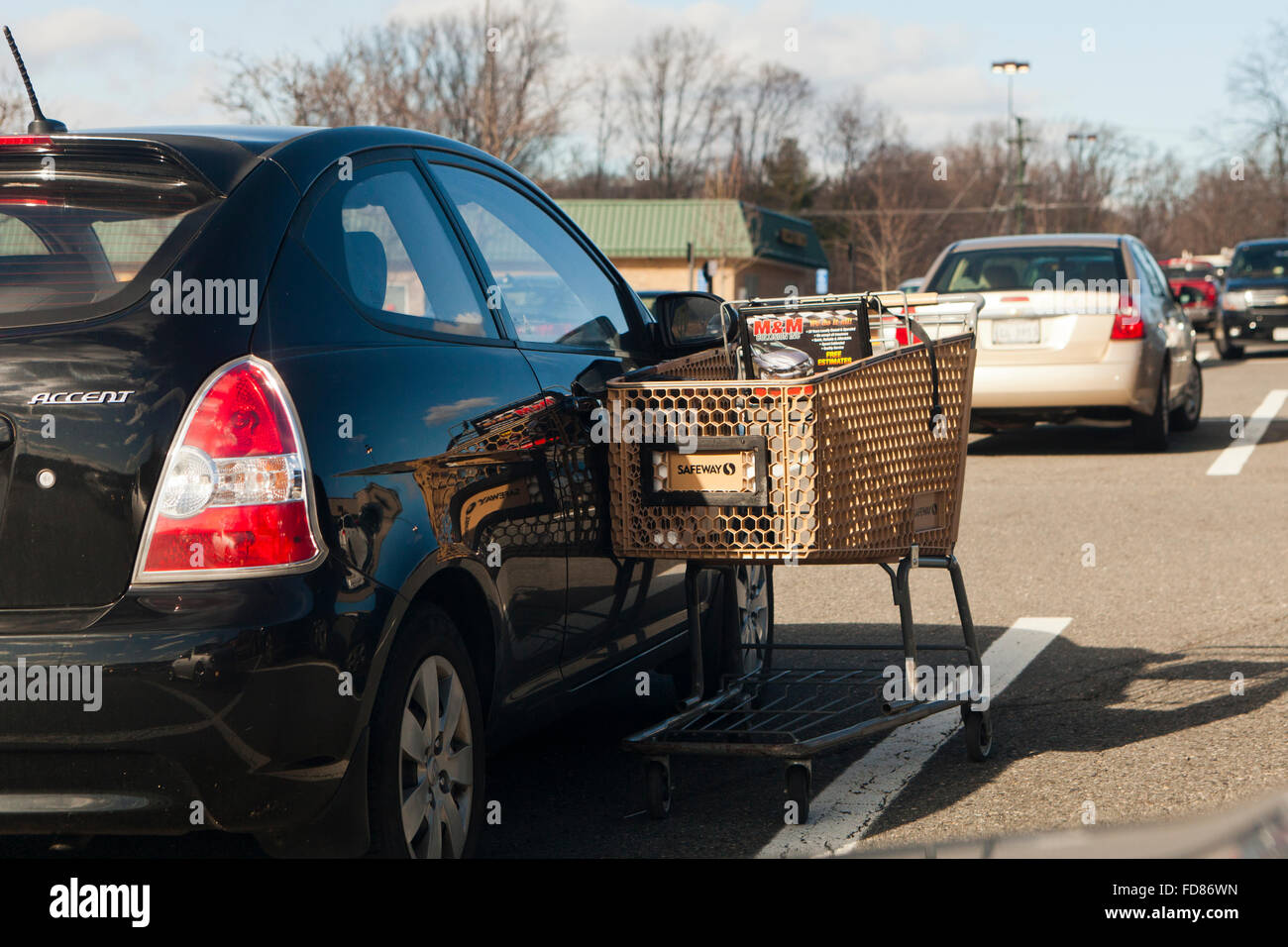 Grocery shopping cart leaning on parked car - USA - Stock Image