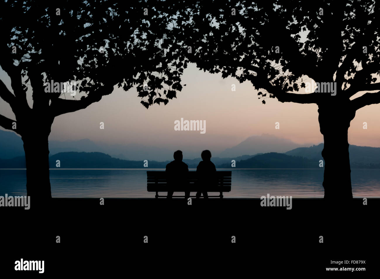 Silhouette Couple Sitting On Bench By Calm Lake At Dusk - Stock Image
