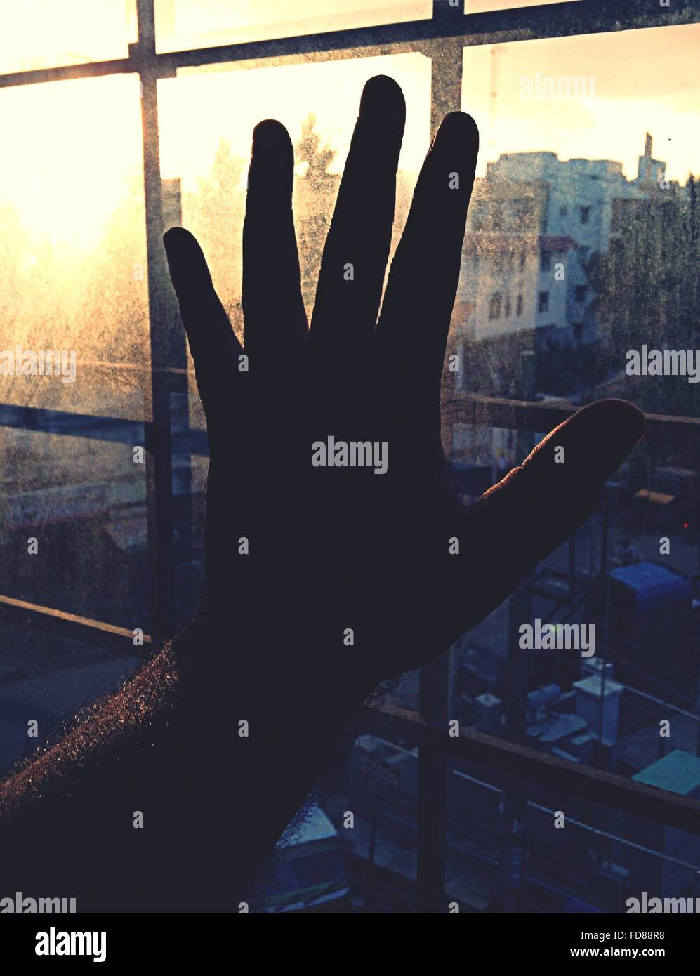 Close-Up Of Silhouette Hand On Window Against Cityscape - Stock Image