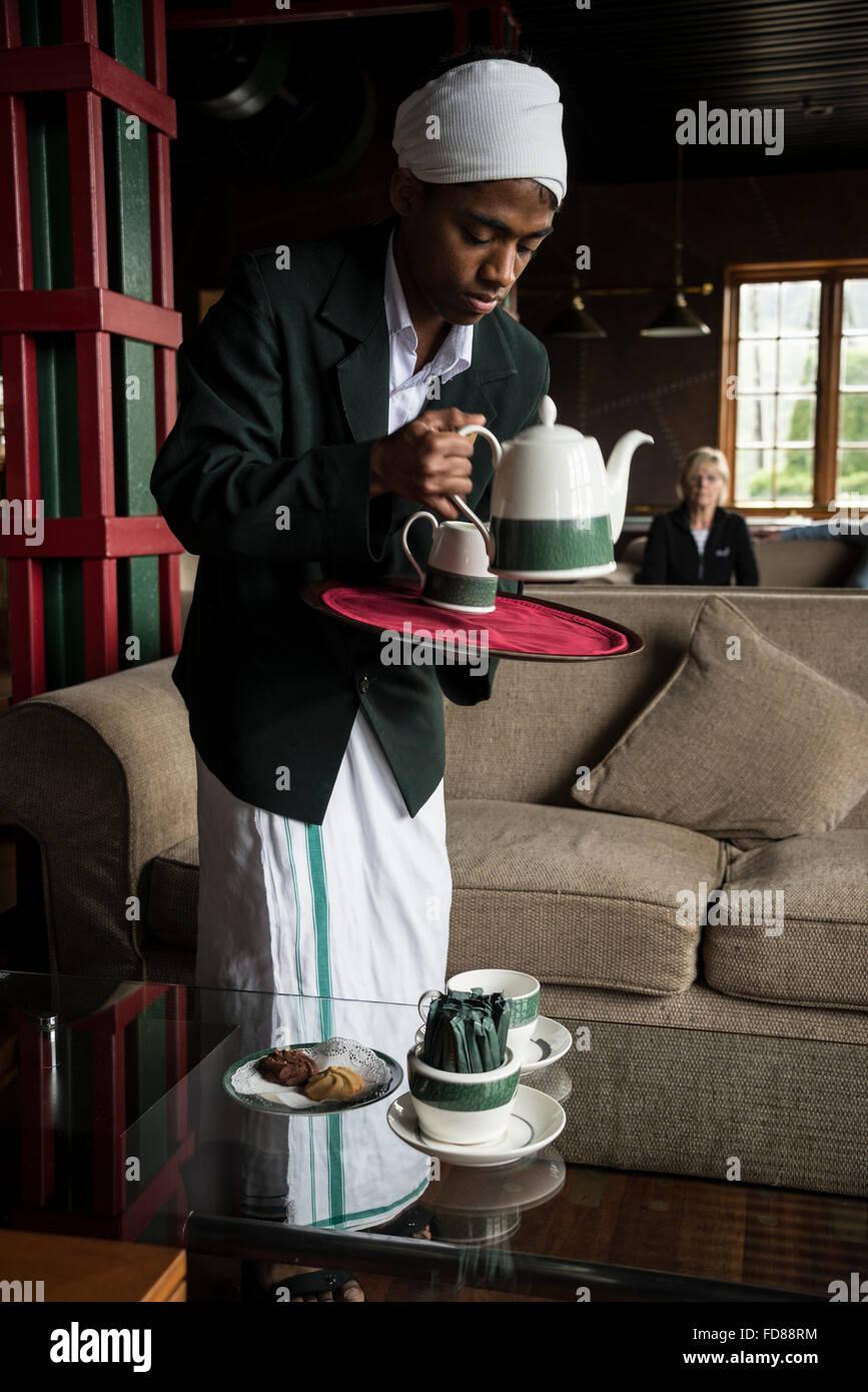 A tea boy serving home produced tea at  the 4-star Heritage Tea Factory hotel above Nuwara Eliya, Central Province, - Stock Image