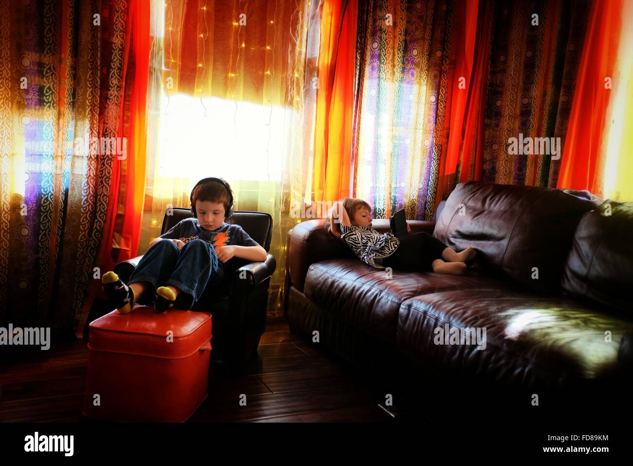 Siblings Relaxing At Home - Stock Image