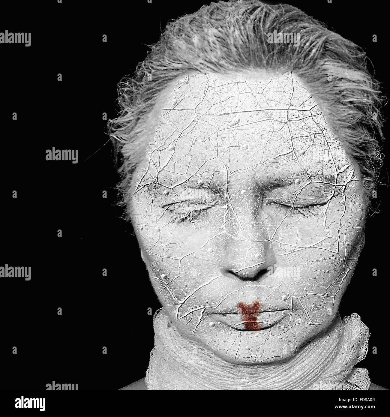 Close-Up Woman With Clay Covered Face Against Black Background - Stock Image
