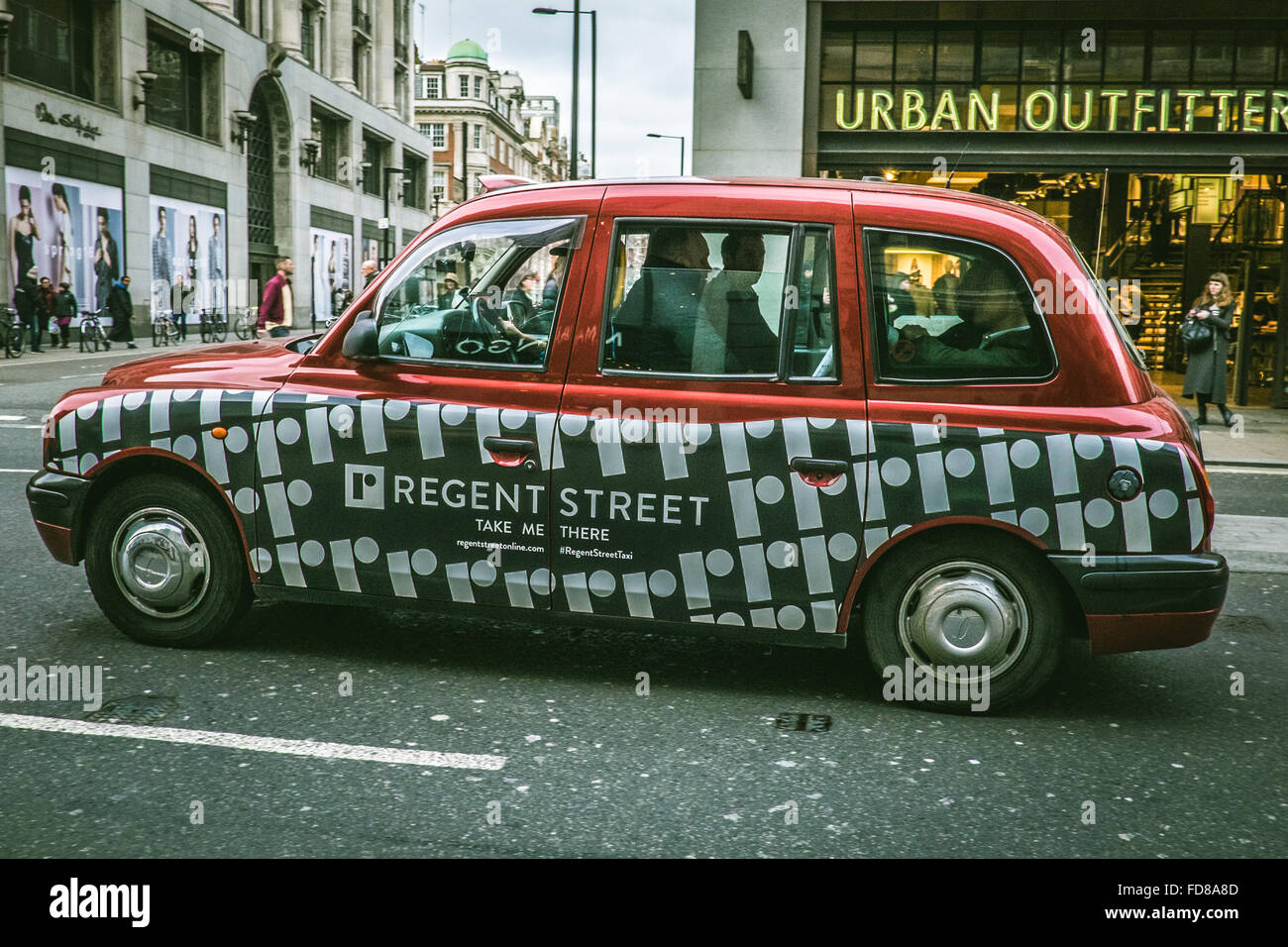 A London Taxi Cab with red and white livery for Regent Street in Oxford Street Stock Photo