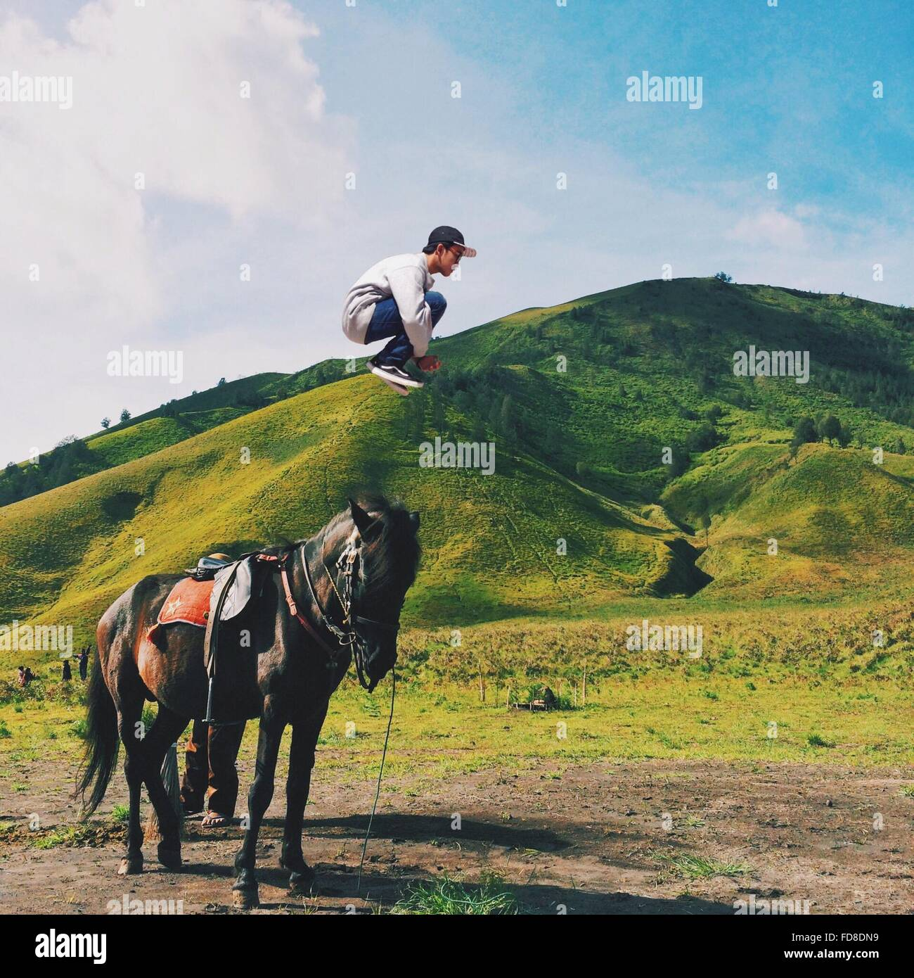 Side View Of Man Jumping In Mid Air Against Green Mountains - Stock Image