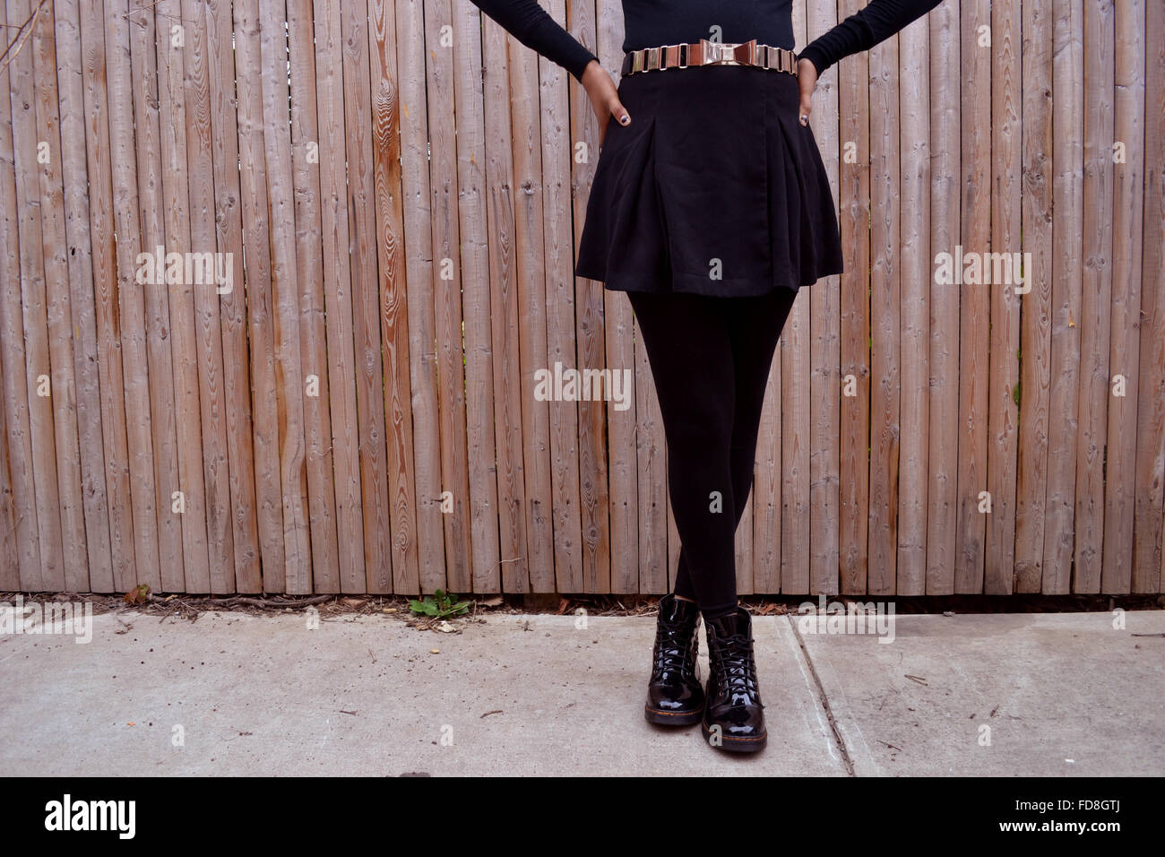 Low Section Of Woman Standing On Sidewalk With Legs Crossed At Ankle Against Wooden Fence - Stock Image