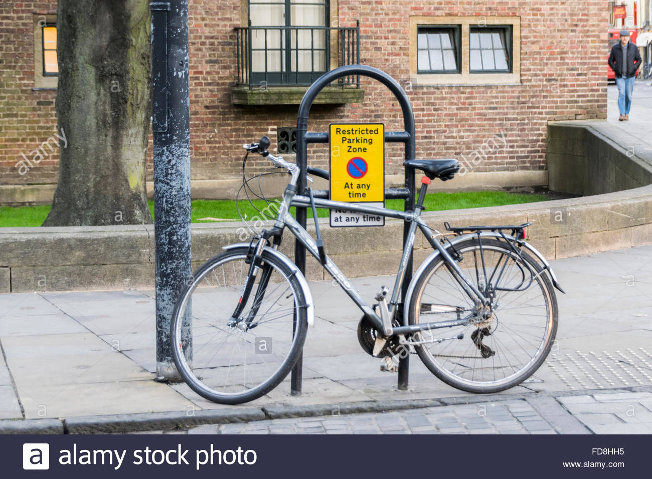 Bicycle locked to a metal post with a restricted parking zone sign - Stock Image
