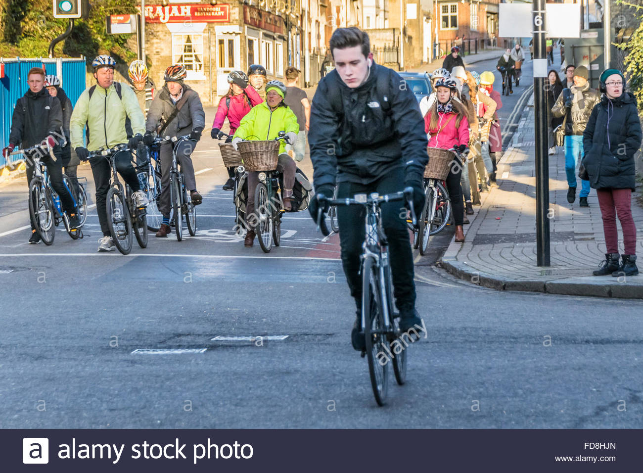 A lone cyclist makes a break for it as other cyclists wait at the traffic lights in the morning on Bridge Street, Stock Photo