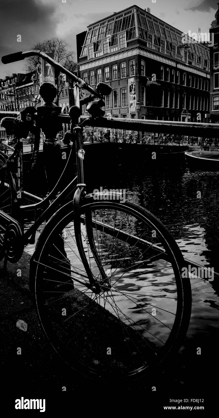 Bicycle Parked On Bridge With Buildings In Background - Stock Image