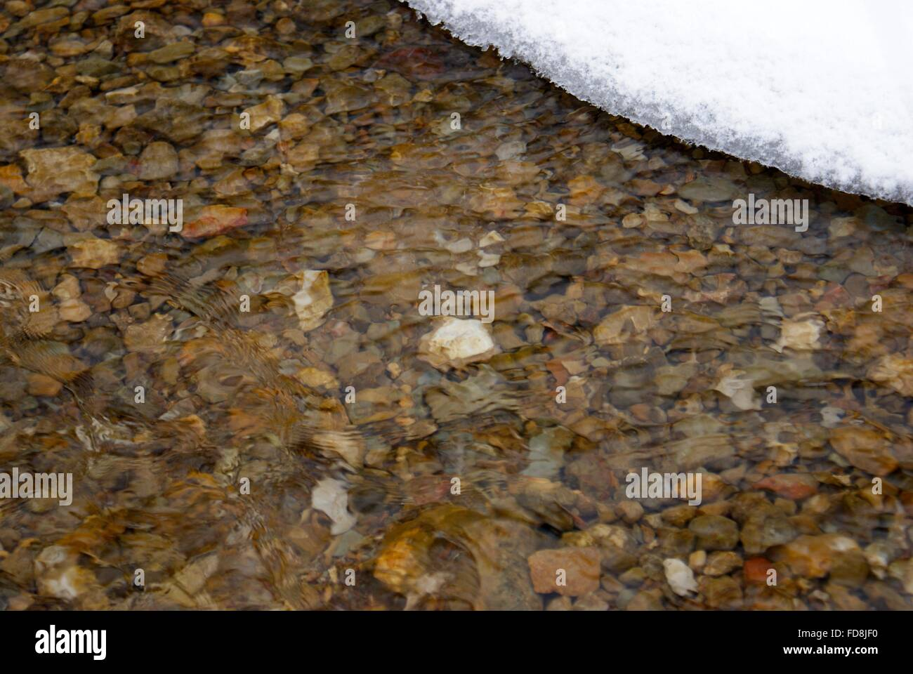 The rocky bottom of a creek running with cold brisk snow water. - Stock Image