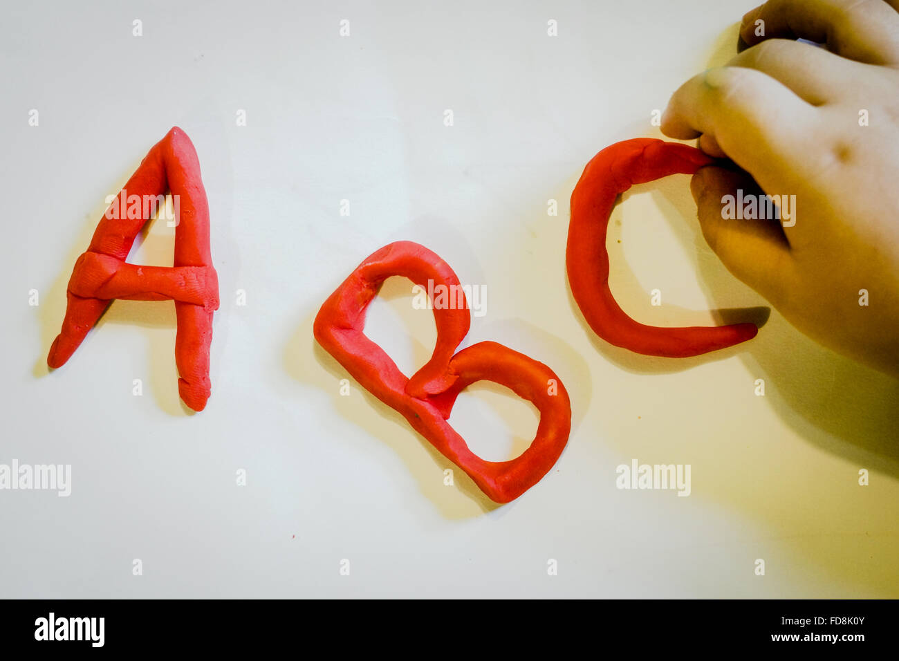 Cropped Hand Making Alphabets With Modelling Clay On White Table - Stock Image