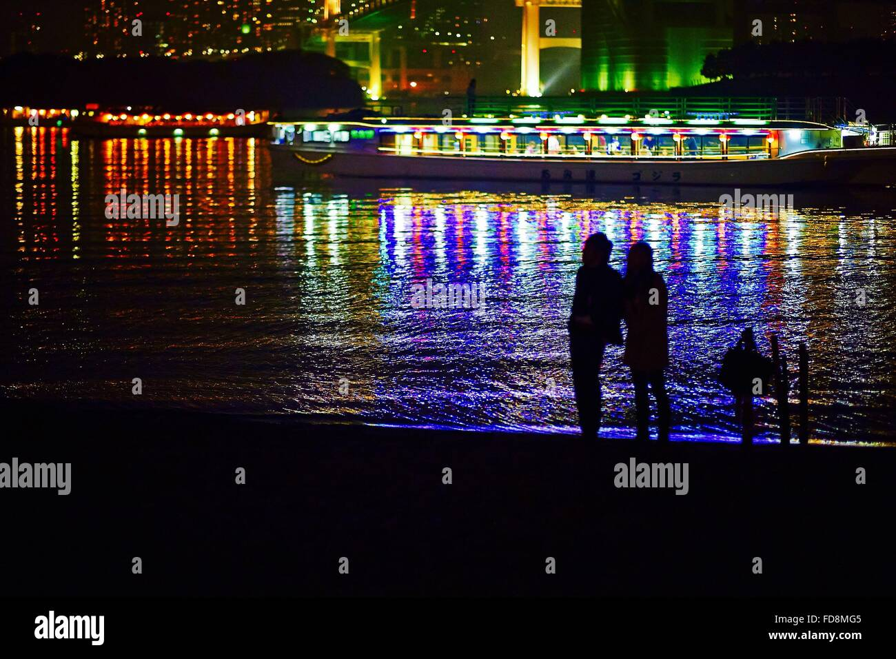 Silhouette People Standing By River With City Reflections At Night - Stock Image