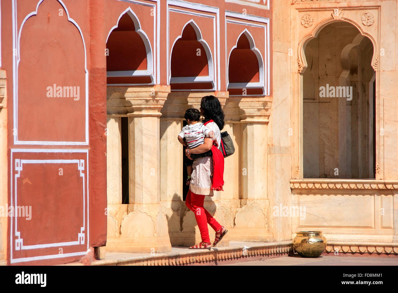 Woman with a child walking at Chandra Mahal in Jaipur City Palace, Rajasthan, India. Palace was the seat of the - Stock Image