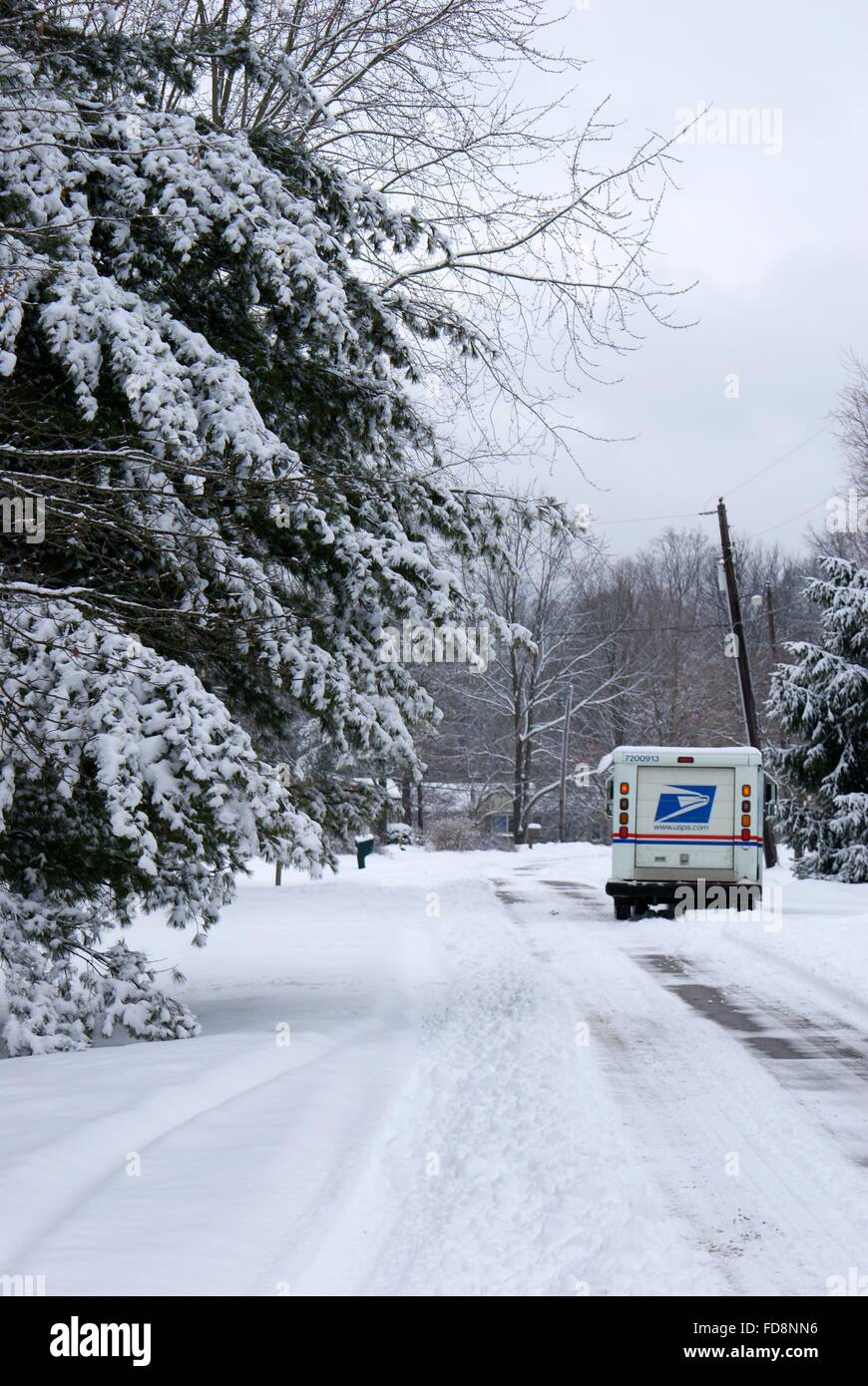 A postal truck delivering mail in a neighborhood in the snow. Stock Photo