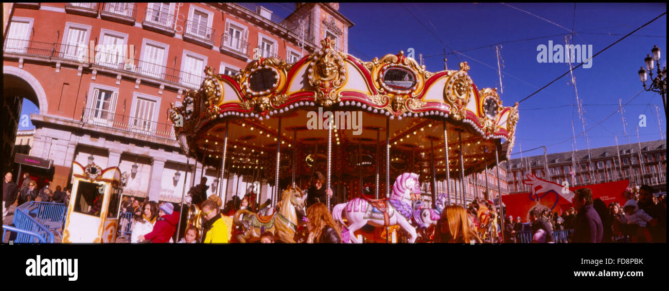 Side View Of Merry-Go-Round Against Building - Stock Image