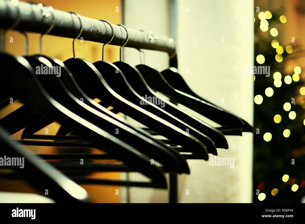 Coat Hangars On Metal Rod Against Defocused Christmas Lights In Office Stock Photo