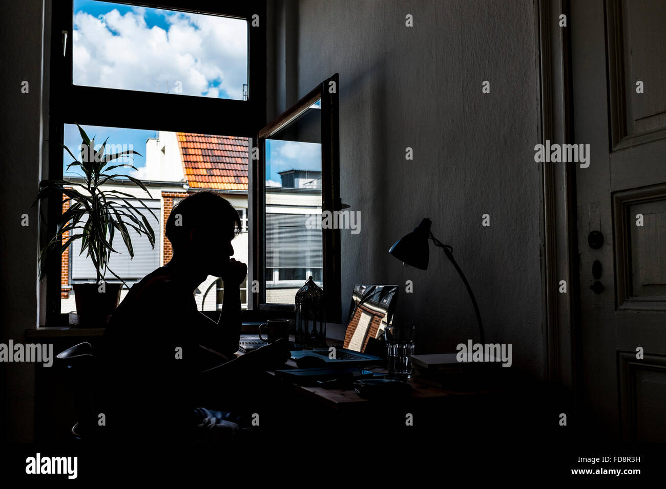 Silhouette Of Man Using Laptop At Desk - Stock Image