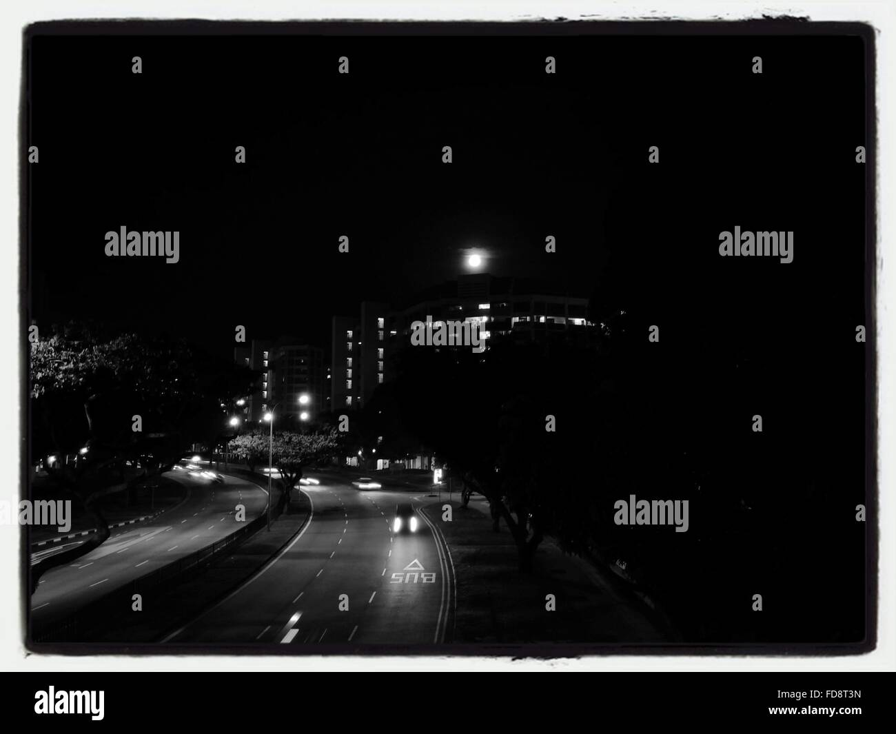 Illuminated Street In City Against Clear Sky At Night - Stock Image