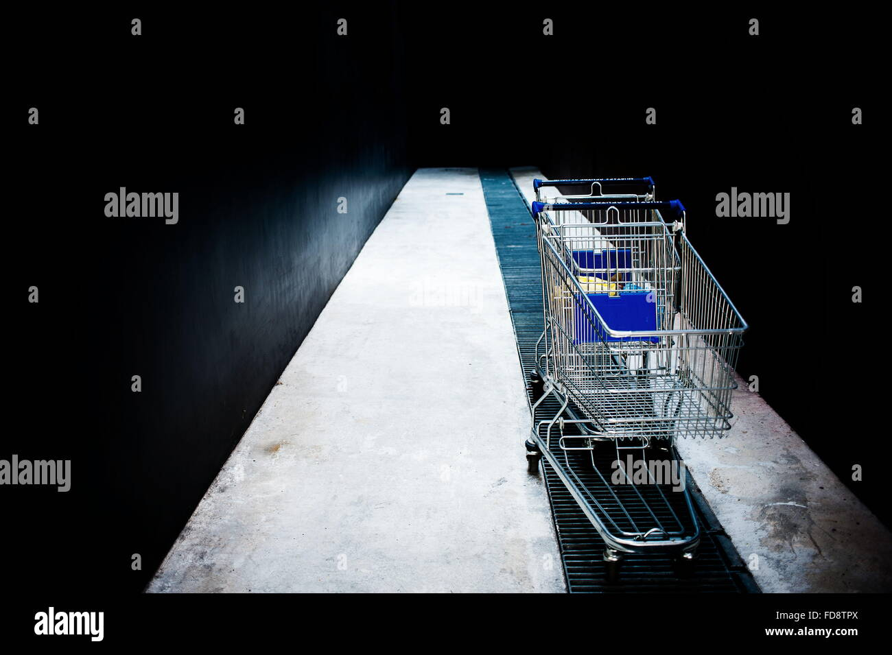 Abandoned Shopping Carts On Metal Grate In Alley - Stock Image