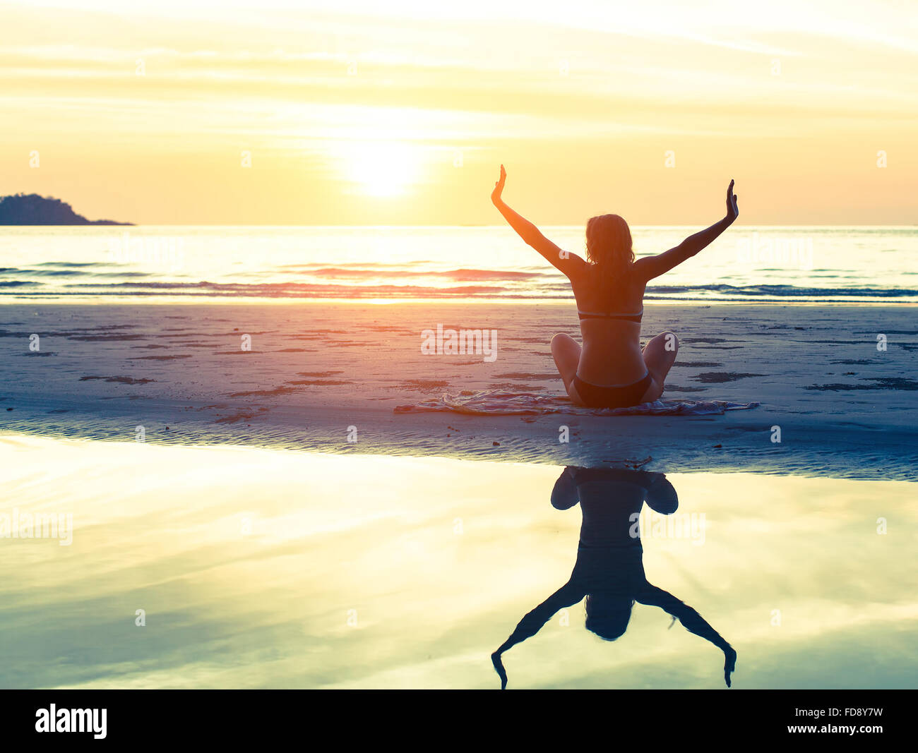 Silhouette of the woman sitting on the beach during amazing sunset, with reflection in the water. Health and Yoga - Stock Image