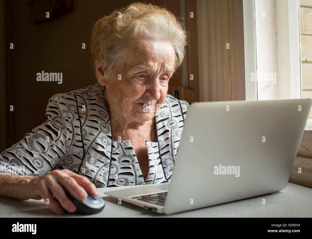 An elderly woman sitting at the table and types on laptop. - Stock Image