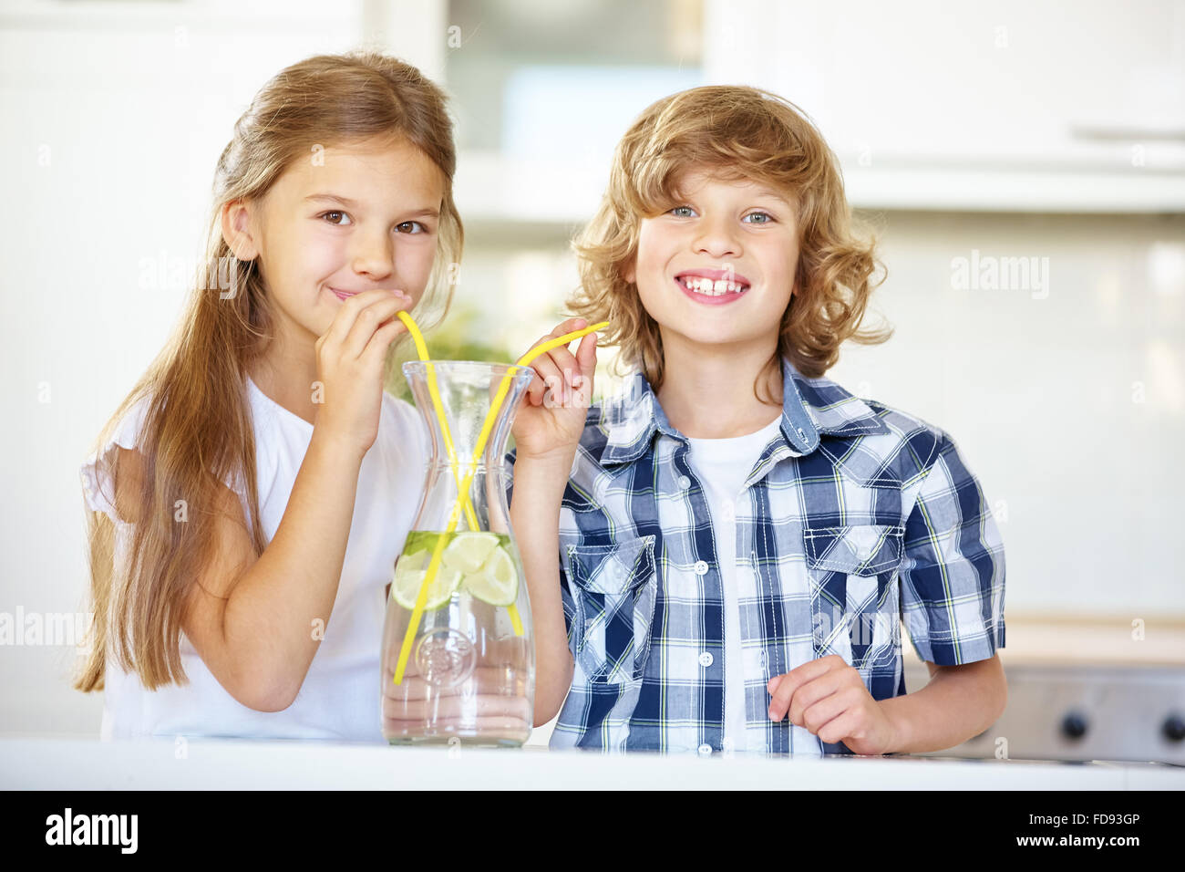 Boy and girl drinking fresh lime water with straw in the kitchen - Stock Image