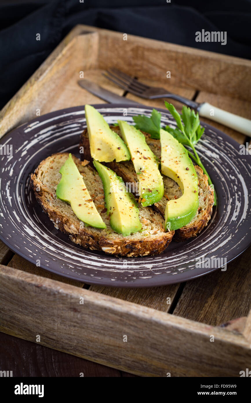 Toasted bread with avocado slices on plate. Healthy breakfast, low calorie diet food, snack or lunch - Stock Image