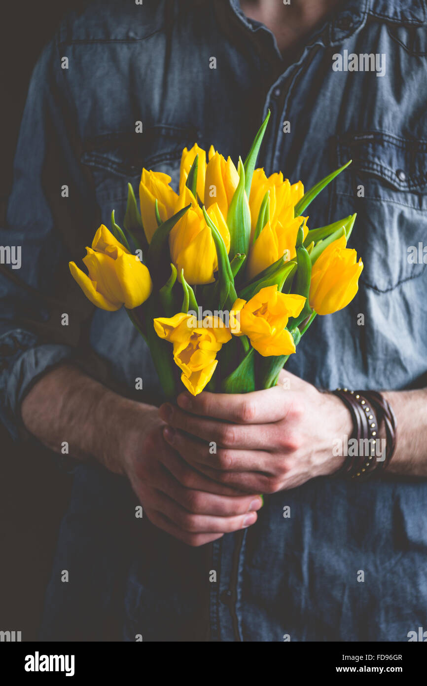 Bouquet flowers hands giving stock photos bouquet flowers hands man holding yellow tulips gift card template poster or greeting card man holding izmirmasajfo