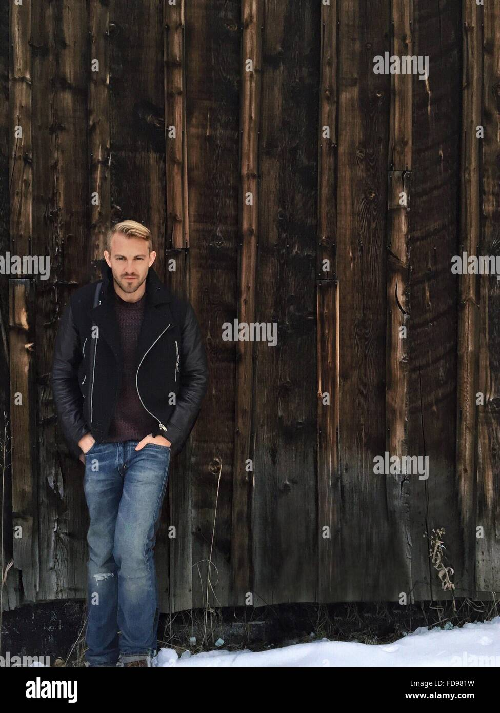 Full Length Portrait Of Young Man Standing On Snowy Landscape Against Wooden Wall - Stock Image