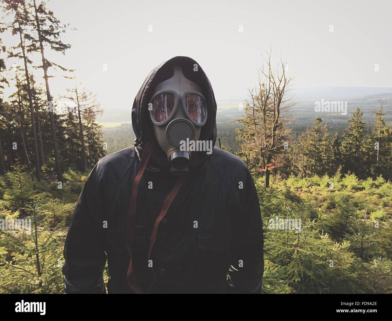 Front View Of Man Wearing Gas Mask In Forest Against Clear Sky - Stock Image