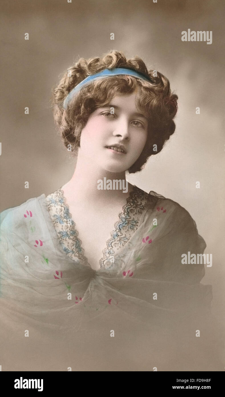 Hand-coloured sepia postcard of a portrait of a beautiful Edwardian woman. - Stock Image