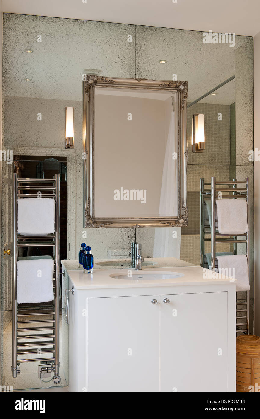 Silver framed mirror above washbasin with heated stainless steel ...