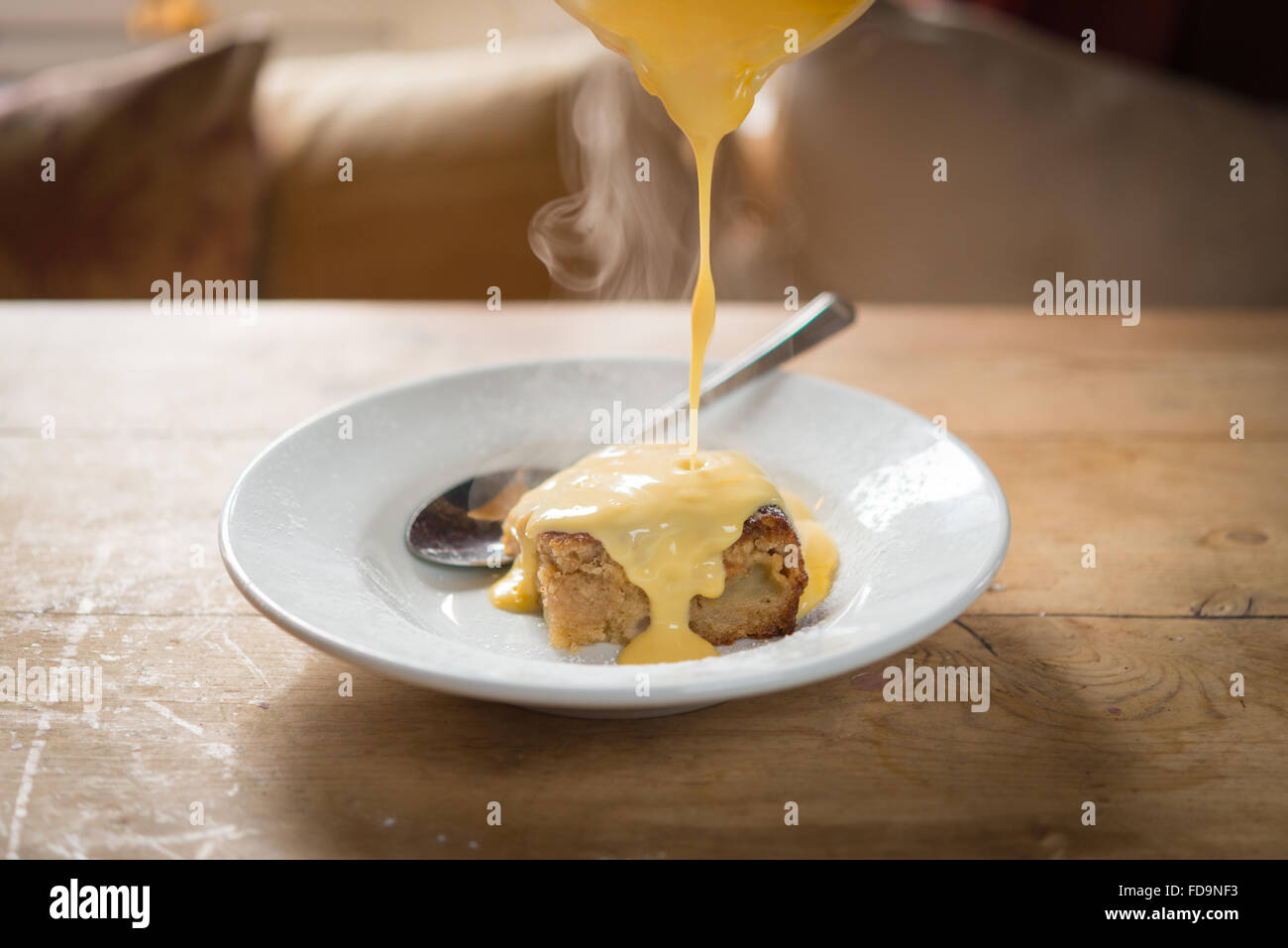A steamed sponge pudding and custard desert on a wooden table - Stock Image