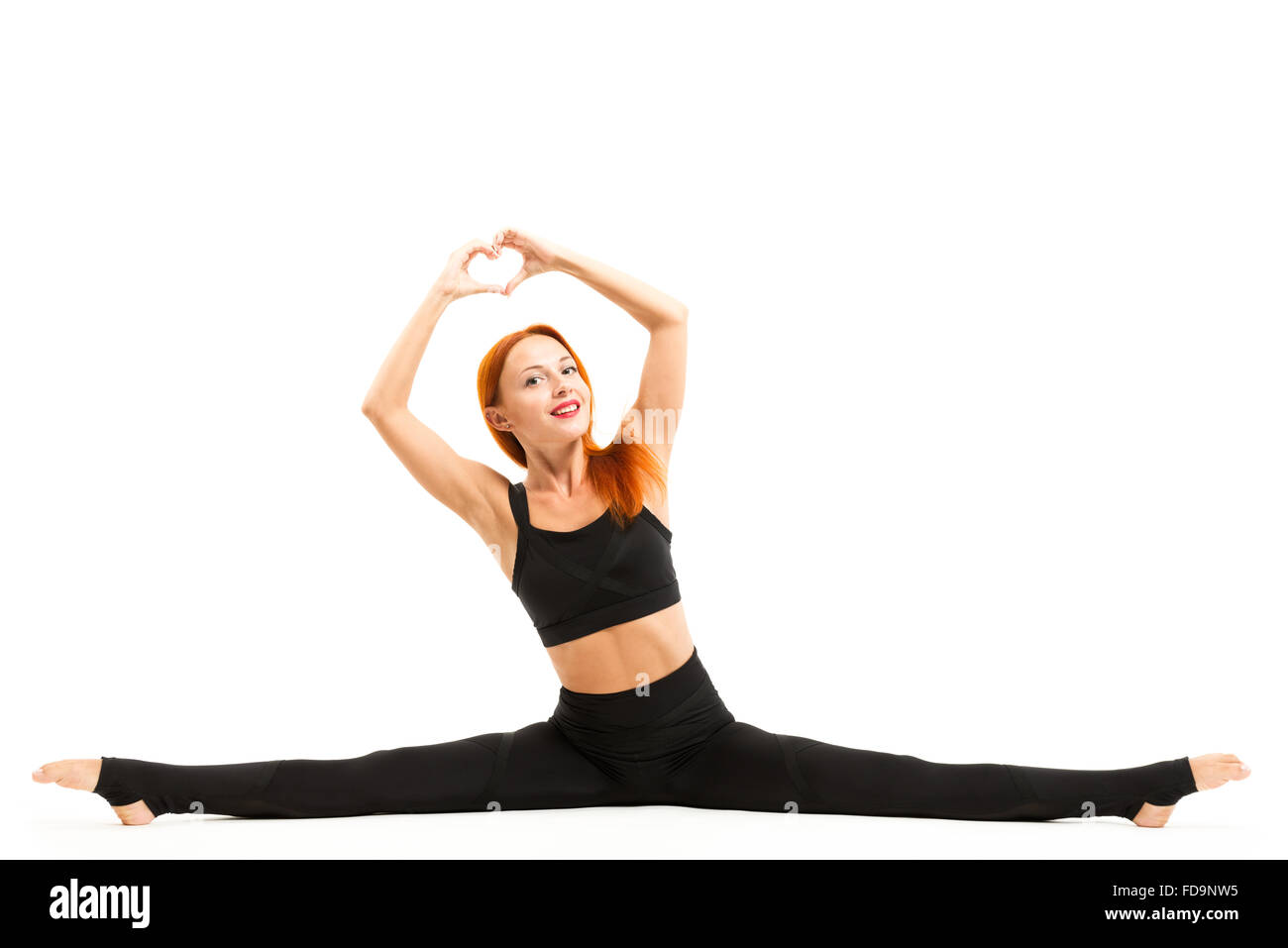 Sporty beautiful young woman wearing sportswear doing yoga splits asana, studio full length view, isolated Stock Photo