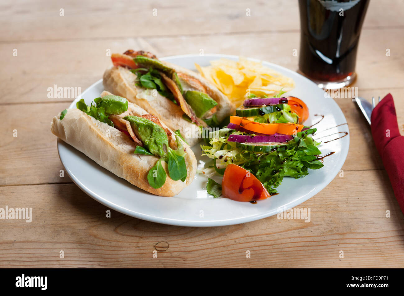 A Bacon lettuce and tomato sandwich and salad on a plate on a wooden table in an English pub. - Stock Image