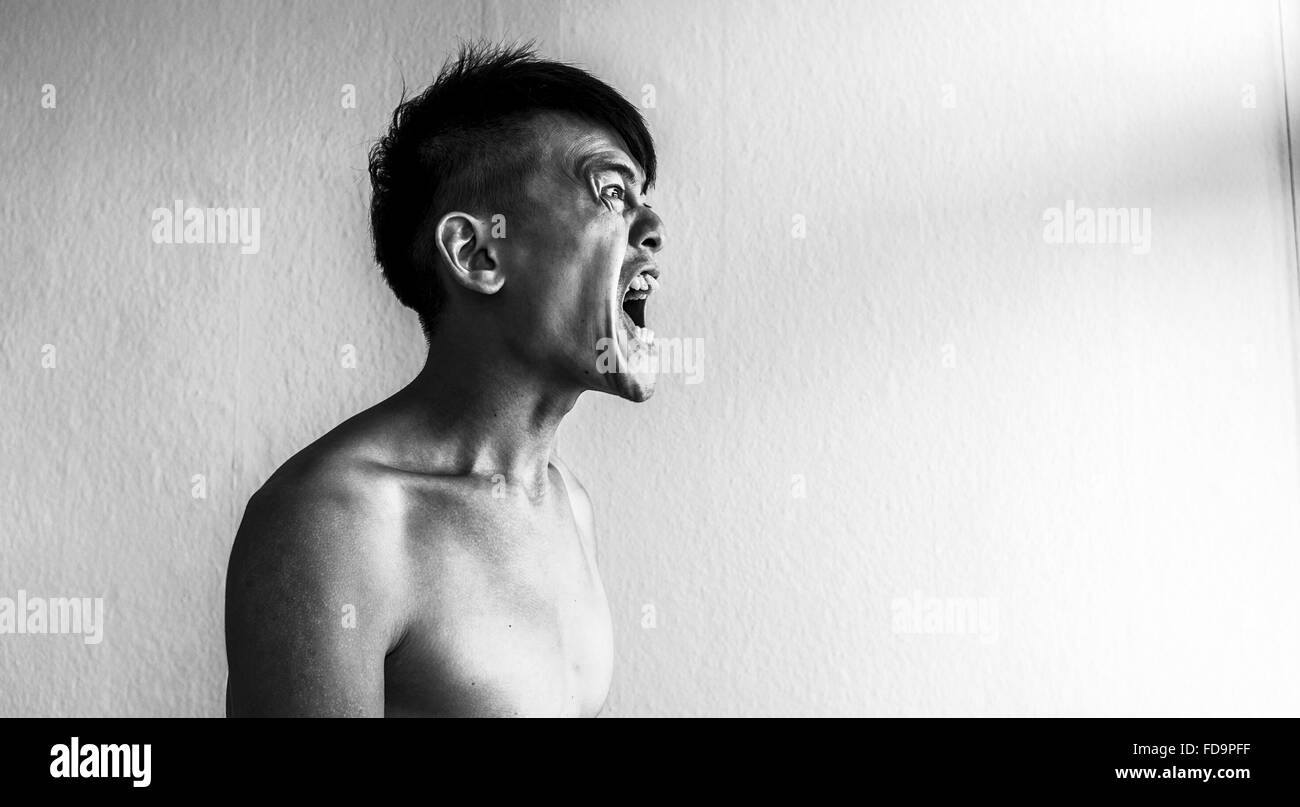 Frustrated Man Screaming At Home - Stock Image